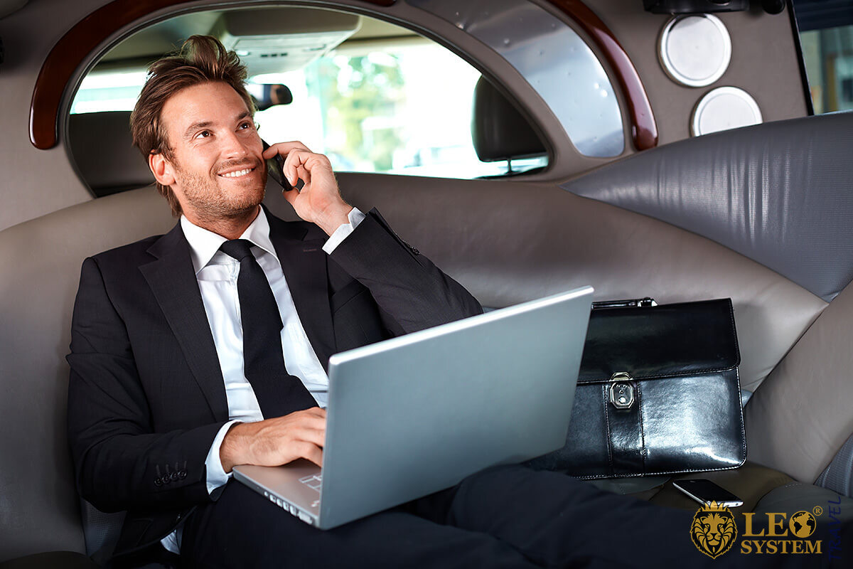 Businessman in car with laptop and phone