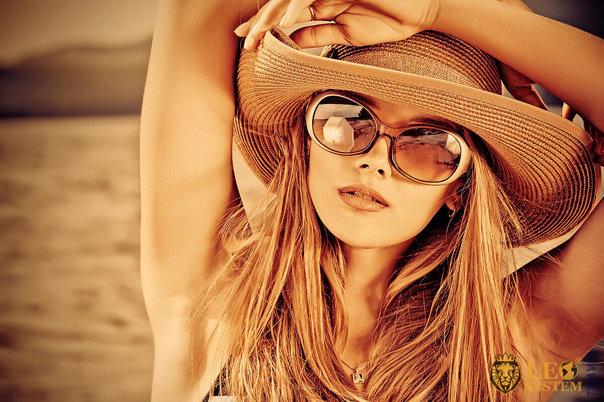 Beautiful woman in hat and glasses