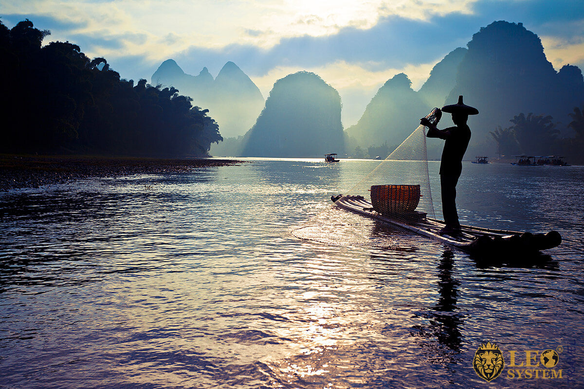 Asian man fishing with a net