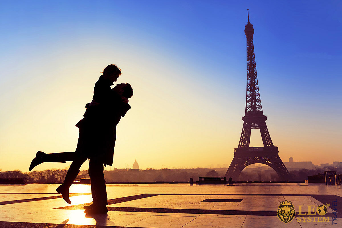 Loving couple kisses on a Eiffel Tower background