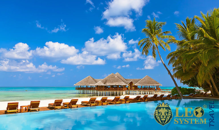 View of the pool, sunbeds and palm trees, Maldives