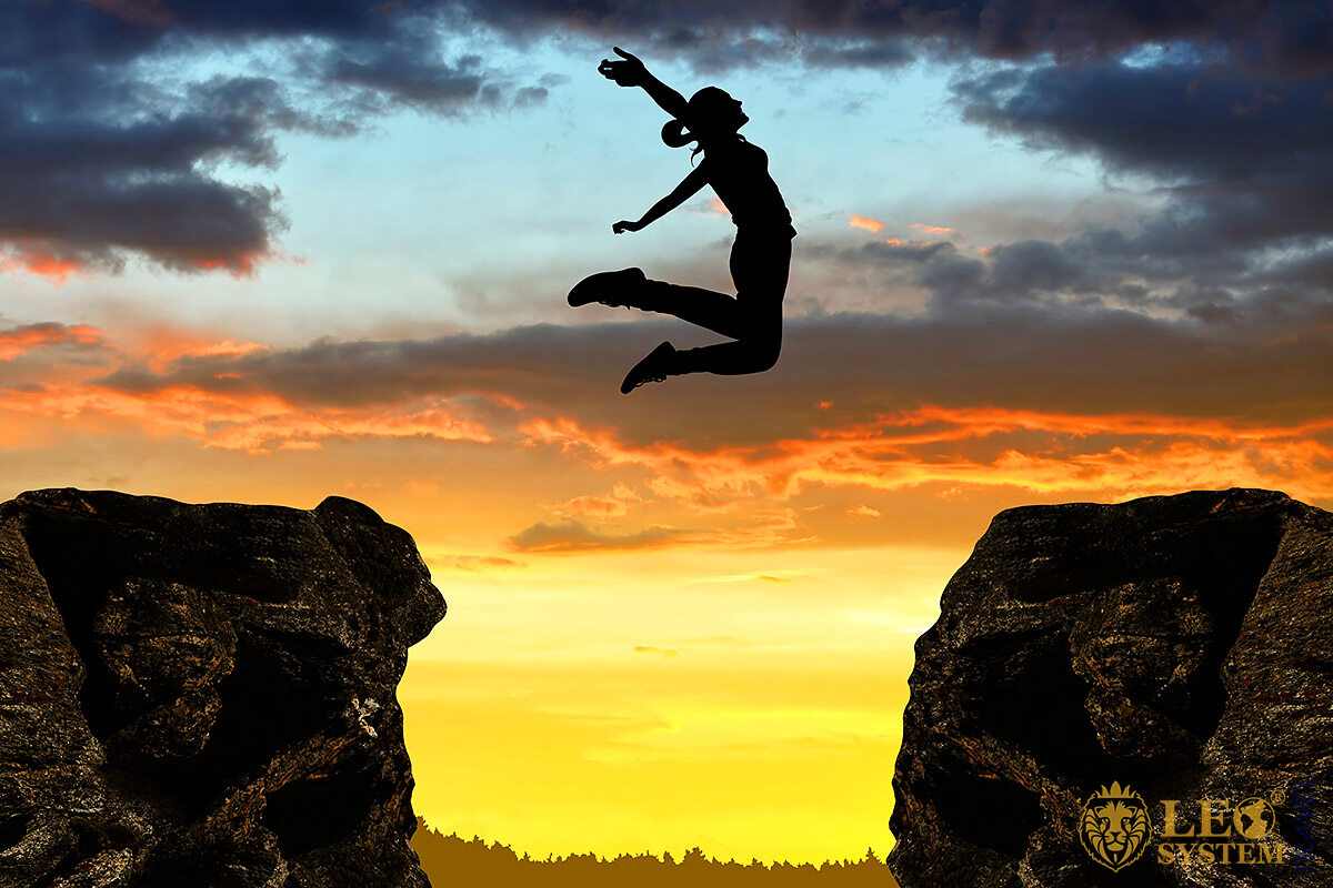 Image of a woman jumping over a cliff from one mountain to another