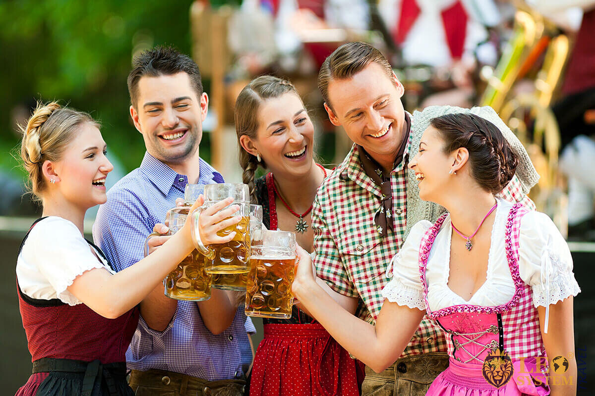 Cheerful company of people raise beer mugs on holiday - Oktoberfest, Germany