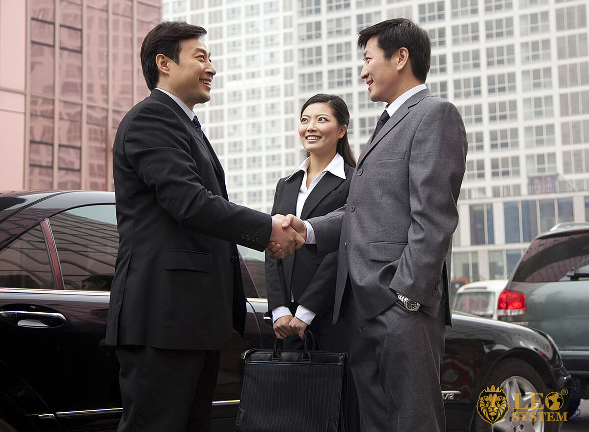 Wealthy Asian businessmen shake hands