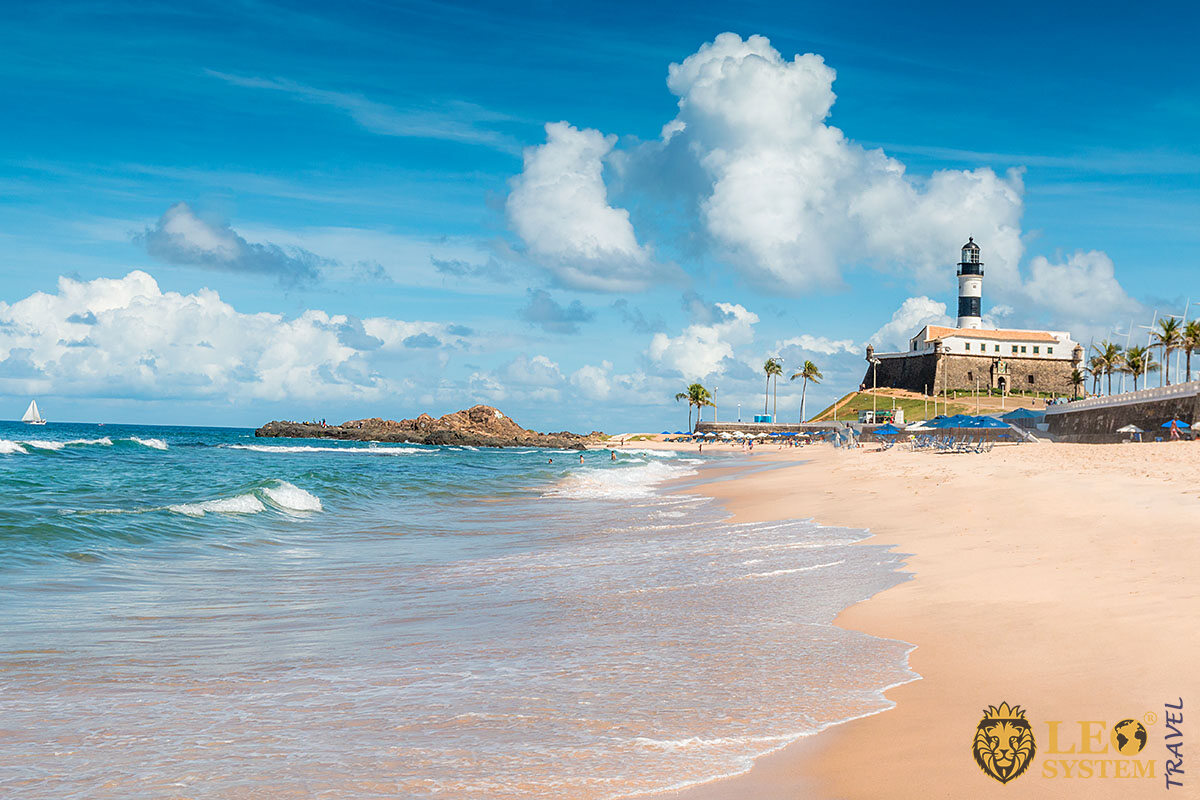View of the beach and Farol da Barra in the city of Salvador, Brazil