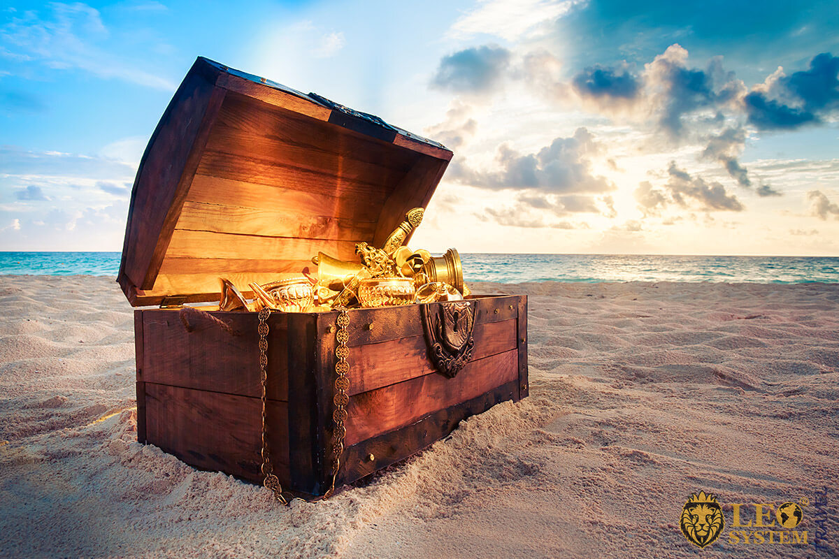 Image of a wooden chest with gold ornaments lying on the sand