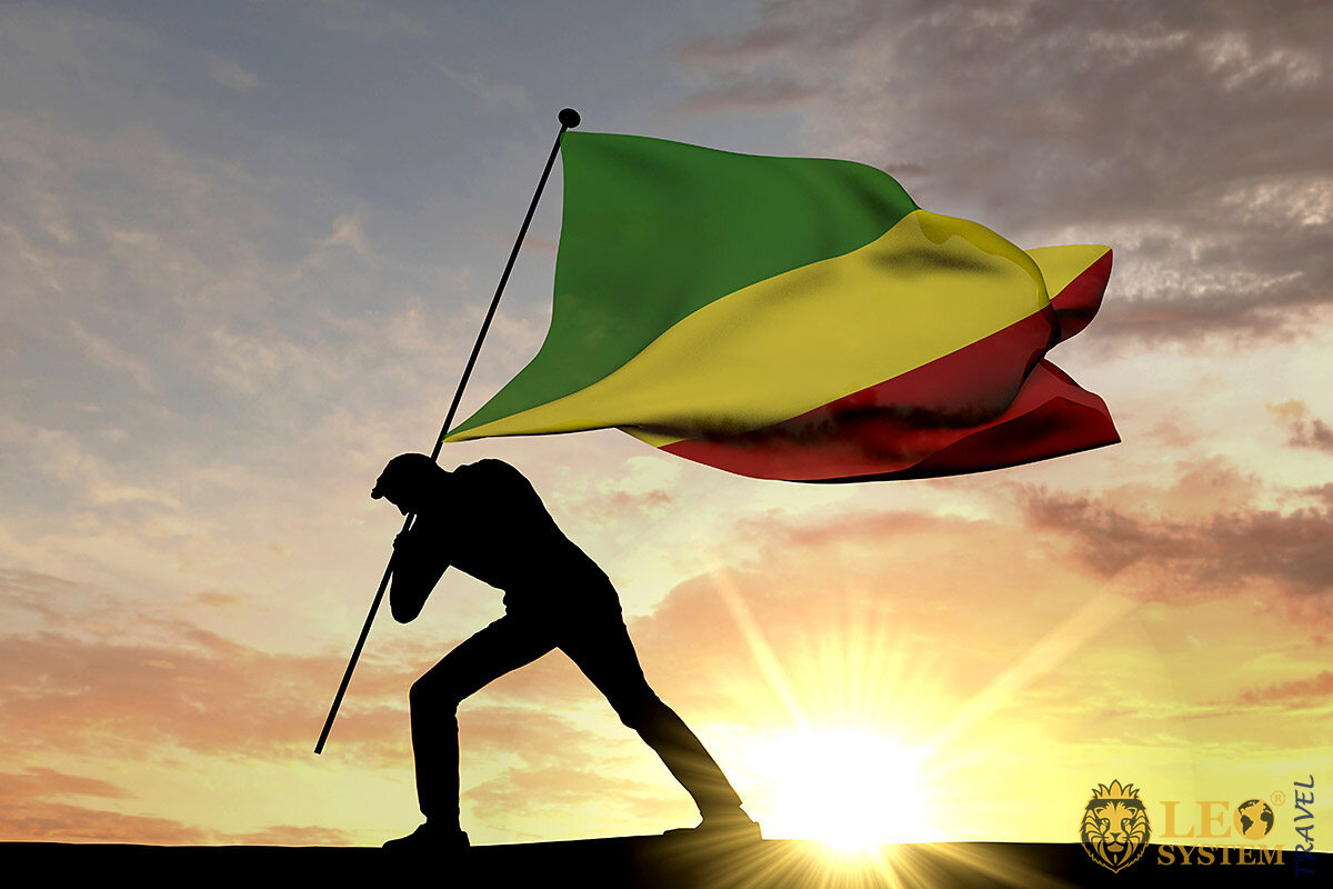 A man walks with the flag of the Republic of the Congo at sunset