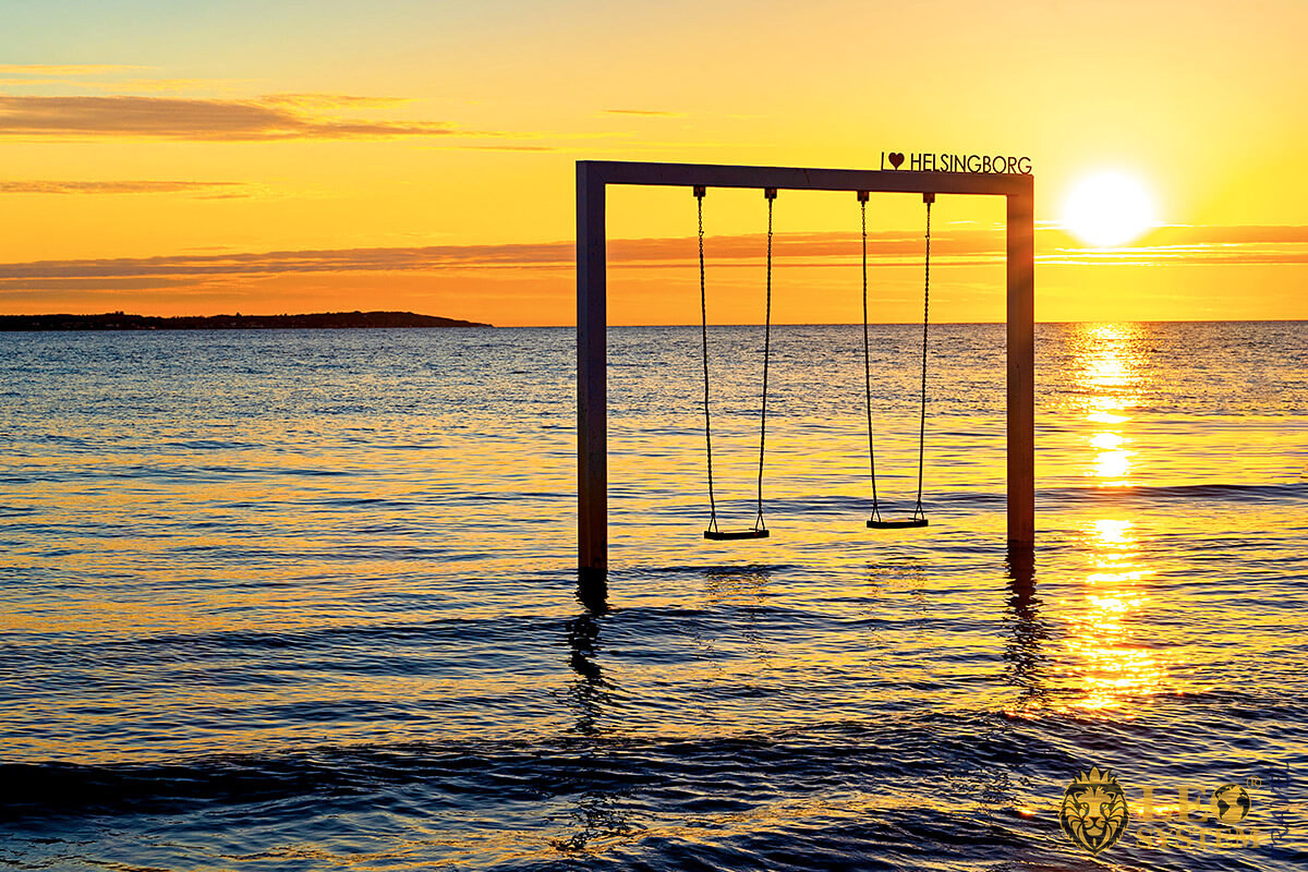 Image of a beach swing in the water at sunset, city of Helsingborg