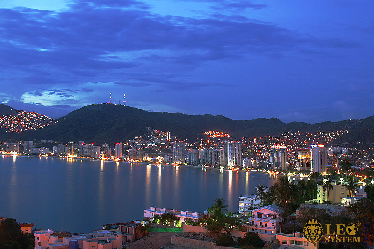 Evening view of mountains, ocean and buildings in Acapulco, Mexico