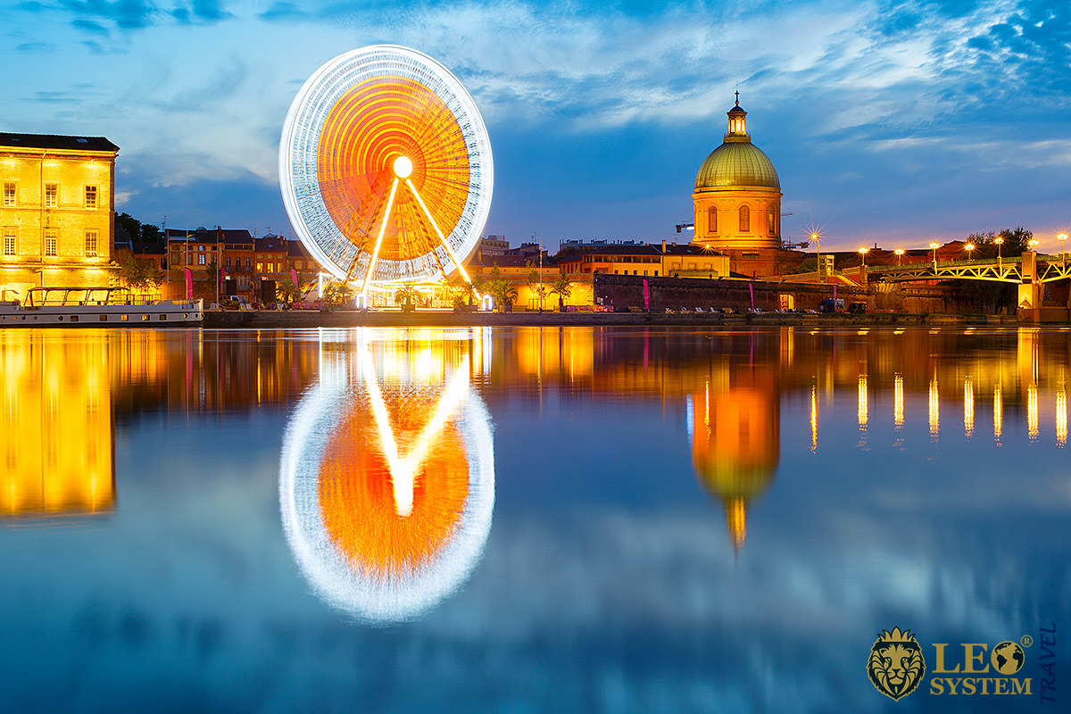 Amazing view of the Ferris Wheel and its reflection in the Garonne River, city of Toulouse