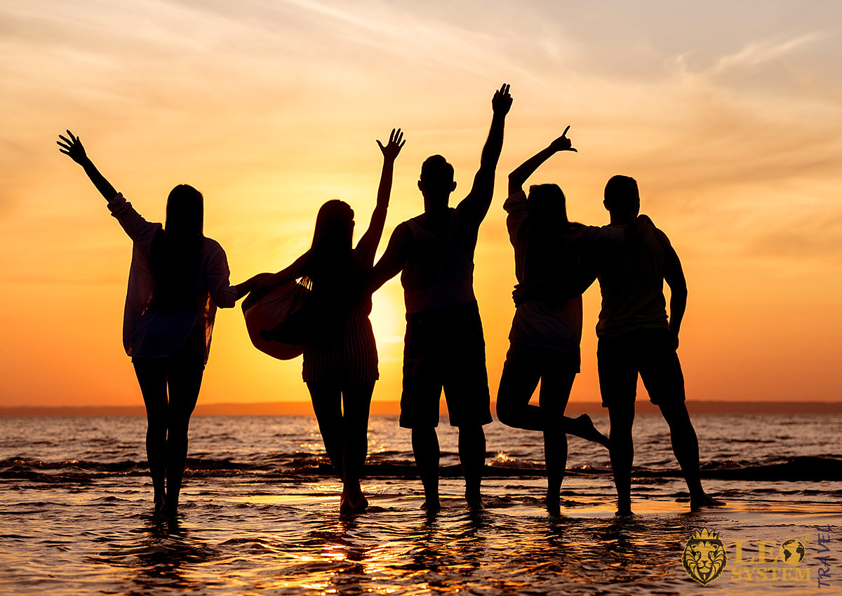 Cheerful group of young people stands in the sea, Ibiza Island, Spain