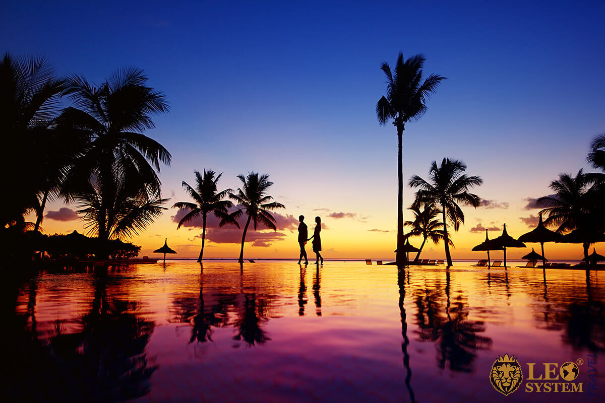 View of a romantic couple and palms by the Pacific Ocean during sunset