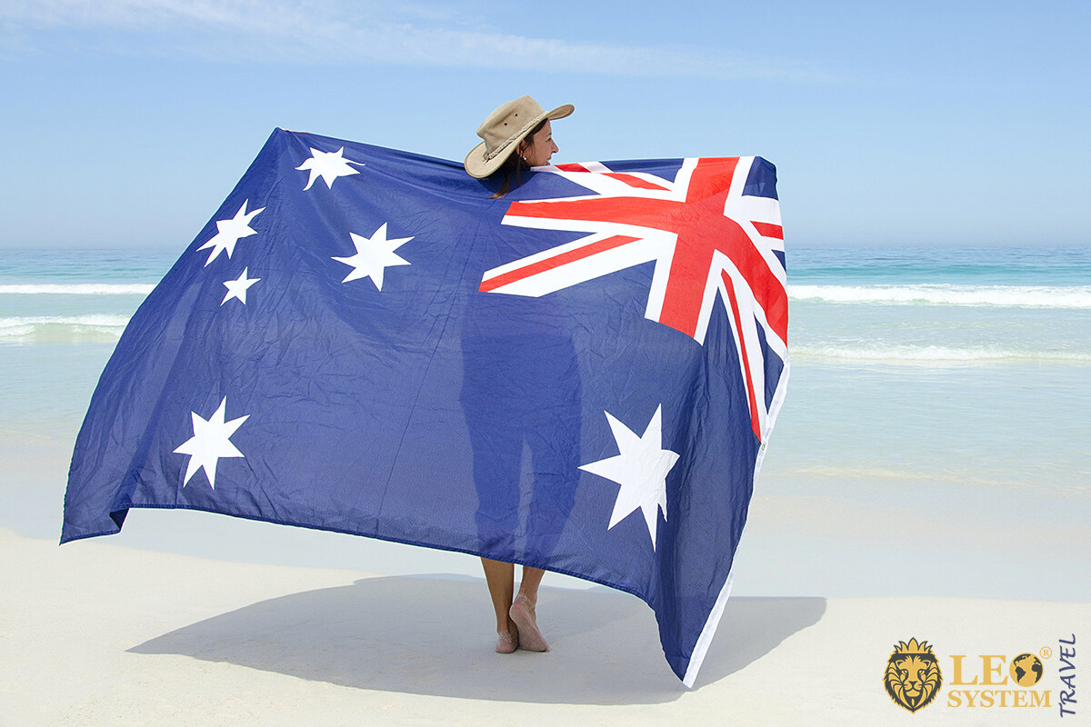Image of a woman on the beach with the Australian flag in her hands